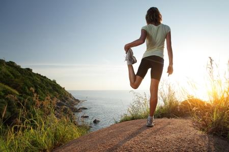 mujer mirando el horizonte: Corredor de fondo se extiende en la cima de una colina y disfrutar de la puesta del sol con vistas al mar Foto de archivo