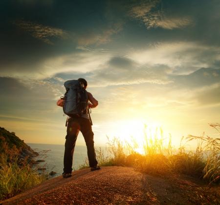 Wanderer mit Rucksack auf einem Felsen und genießen Sonnenuntergang über dem Meer