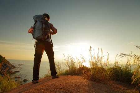 Hiker with backpack standing on a rock and enjoying sunset over sea photo