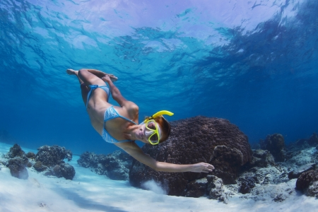 skin diving: Underwater shoot of a woman swimming over sandy sea bottom Stock Photo