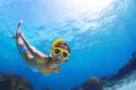 Onderwater spruit van een jonge lachende dame snorkelen en het doen van snorkelen in een tropische zee