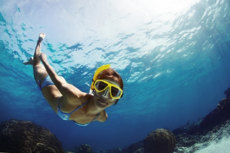 snorkeling: Underwater shoot of a young smiling lady snorkeling and doing skin diving in a tropical sea Stock Photo