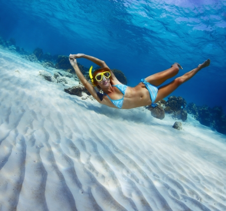 Young lady snorkeling in a transparent tropical sea over sandy bottom Stock Photo - 18043017