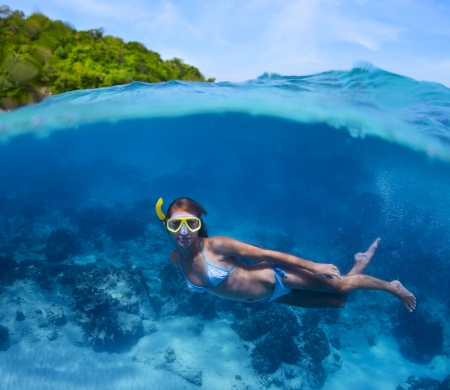 skin diving: Underwater shoot of a young lady doing skin diving in tropical sea with green island on the background Stock Photo