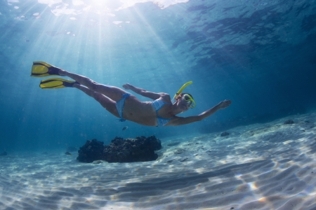 snorkeling: Underwater full length portrait of a woman snorkeling in tropical sea over sandy bottom