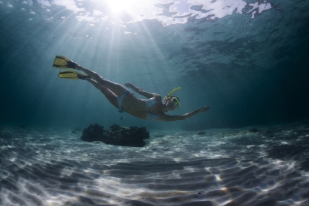 Underwater full length portrait of a woman snorkeling in tropical sea over sandy bottom Stock Photo - 18043068