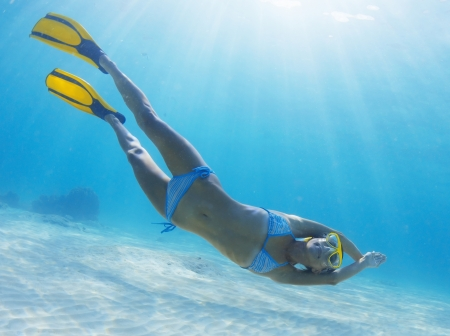 skin diving: Underwater full length portrait of a woman snorkeling in tropical sea over sandy bottom