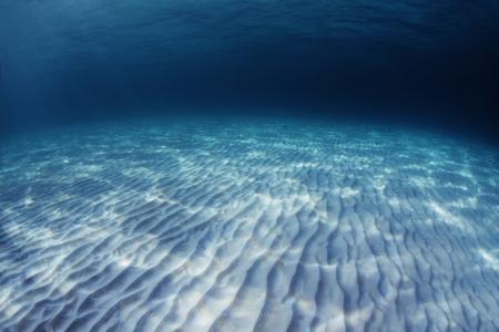 Onderwater schieten van een oneindige zand zeebodem met golven op een zee-oppervlak Stockfoto