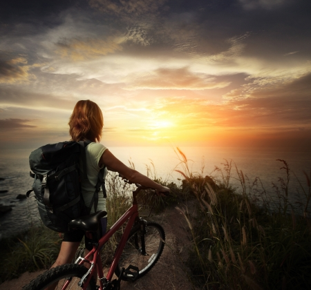 Young woman with backpack standing on ground near her bicycle and enjoying sunset over sea photo