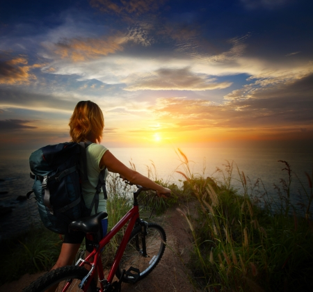 bike tire: Young woman with backpack standing on ground near her bicycle and enjoying sunset over sea