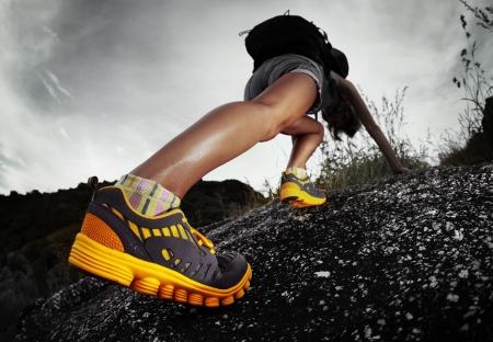 escalando: Caminante con mochila de escalada terreno rocoso. Enfoque en el arranque