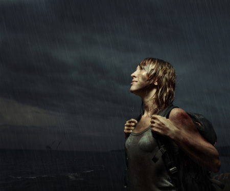 mud woman: Portrait of a woman with backpack standing on the rain with wet dirty clothes and wet hair with bloody bruises on arm