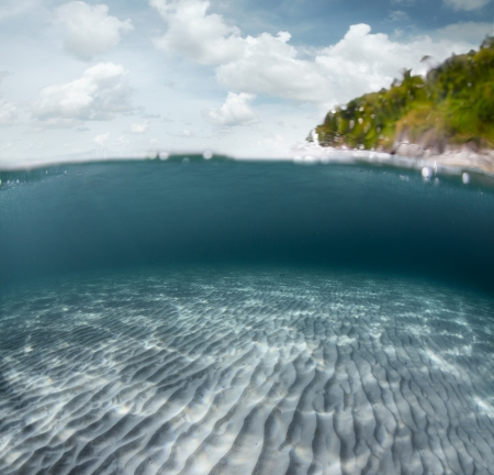 Underwater shoot of a sandy sea bottom and green tropical island with cloudy sky above sea surface Stock Photo - 18028138