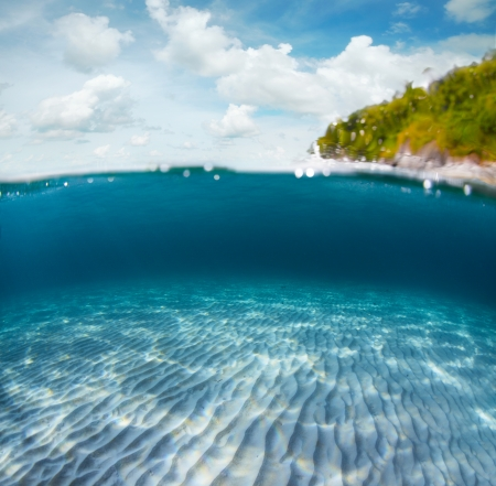 rippled: Underwater shoot of a sandy sea bottom and green tropical island with cloudy sky above sea surface