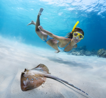 Underwater shoot of a young lady snorkeling and doing skin diving over sandy sea bottom with blue spotted ray on the foreground Stock Photo