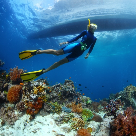 Underwater shoot of a young lady snorkeling and diving on a breath hold over vivid coral reef of tropical island with boat silhouette on surface photo