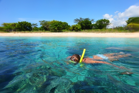 Young lady snorkeling in a tropical sea photo