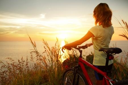 海海岸の自転車の側に立って、夕日を楽しむ若い女性