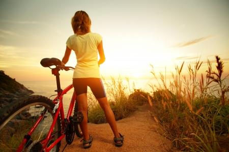 vida natural: Dama joven de pie con la bicicleta en una costa del mar y disfrutar de la puesta del sol