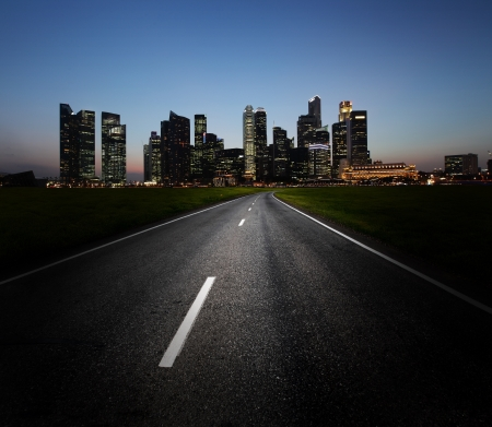 Asphalt road and city with illuminated buildings on the horizon photo