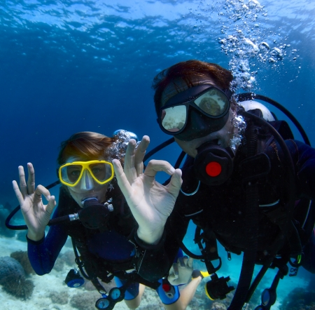 Scuba divers underwater showing ok signal photo