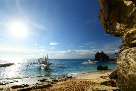 apo: Traditional philippine boat Bangka anchored opposite cliff. Apo island