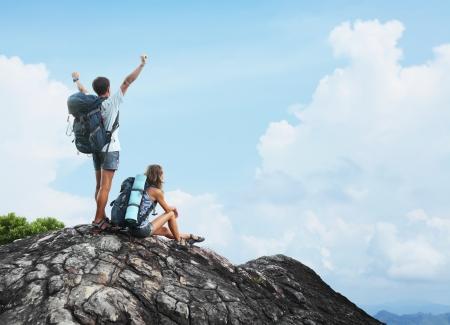 山の頂上からの眺めを楽しんでいるバックパックと 2 つのハイカー