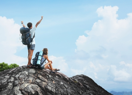 trek: Two hikers with backpacks enjoying view from top of a mountain