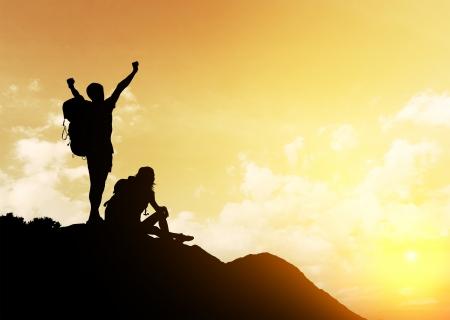 escalada: Silhuetas de dois caminhantes com mochilas que aprecia a vista do por do sol do alto de uma montanha Banco de Imagens