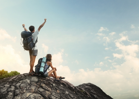 Two hikers with backpacks enjoying view from top of a mountain photo