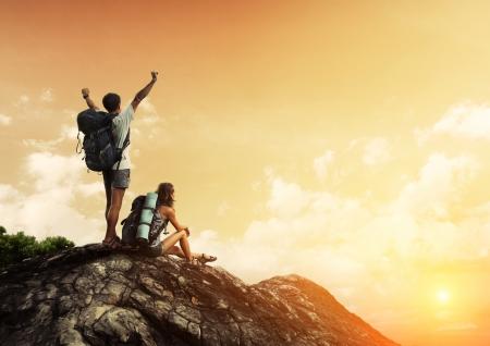 bergbeklimmen: Twee wandelaars met rugzakken genieten van zonsondergang uitzicht vanaf de top van een berg