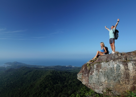 Young hikers with backpacks relaxing on top of a mountain and enjoying valley view photo