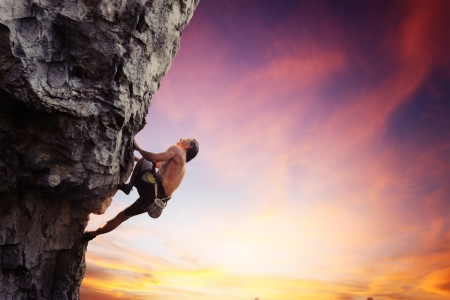 belay: Young man climbing natural rocky wall with sunset sky on the background