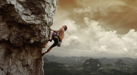 Young man climbing natural rocky wall with tropical valley on the background