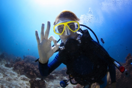 underwater sport: Underwater shoot of a woman diving with scuba and showing ok signal Stock Photo