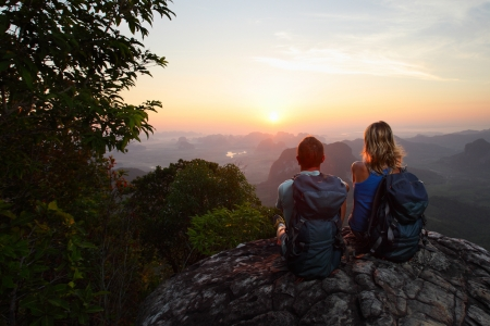 Hikers with backpacks relaxing on top of a mountain and enjoying sunrise photo