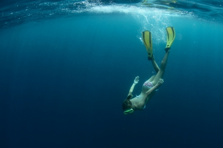 Young lady snorkeling and enjoying skin diving in a tropical sea photo