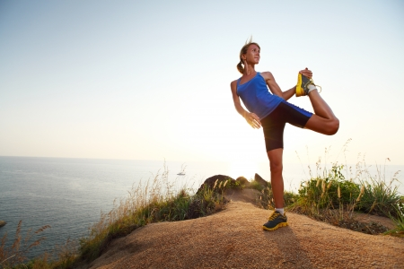 woman hiking: Young slim lady doing stretching exercises on a rural path with grass Stock Photo