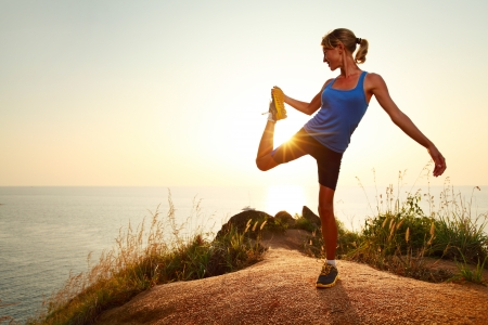stretching: Young slim lady doing stretching exercises on a rural path with grass Stock Photo