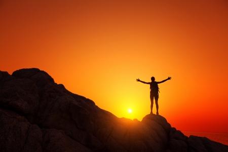 Юный турист с рюкзаком стоя на скале и наслаждаясь закатом