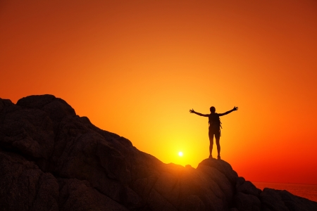 バックパックの岩の上に立っていると夕日を楽しむ若い観光客