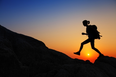 Young lady with backpack walking through rocky terrain at sunset Stock Photo - 19362514