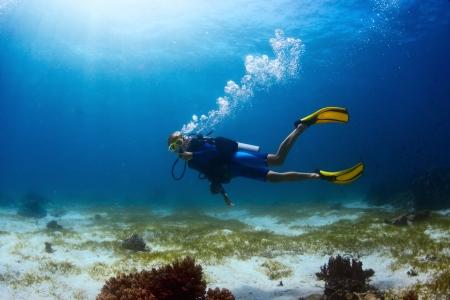 Scuba duiker tropische duikplaats en vinnen op de billetjes