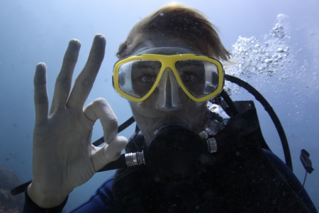 woman diving: Underwater shoot of a woman diving with scuba and showing ok signal Stock Photo