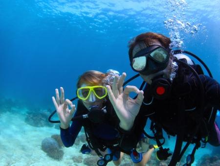 picada: Buzos bajo el agua muestran se?de ok Foto de archivo