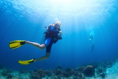 picada: Disparar bajo el agua de un buzos nadando en un agua azul claro Foto de archivo