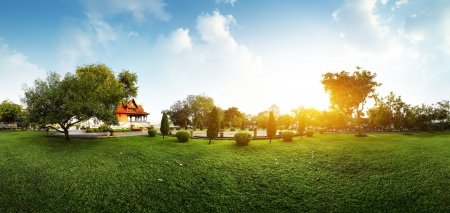 equirectangular: Panorama of a green garden with buddhist building and meadow with grass at early morning Stock Photo