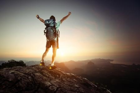 Wanderer mit Rucksack steht auf der Spitze eines Berges mit erhobenen Händen und genießen Sonnenaufgang