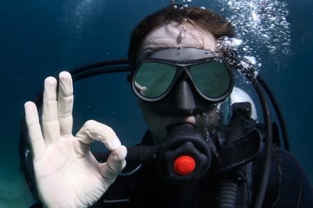 scuba goggles: Underwater shoot of a man diving with scuba and showing ok signal