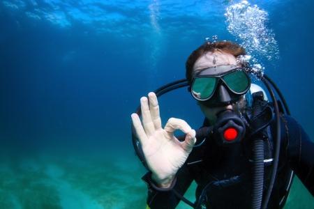 Disparar bajo el agua de un hombre de buceo con escafandra aut?noma y mostrando la se?al se puede